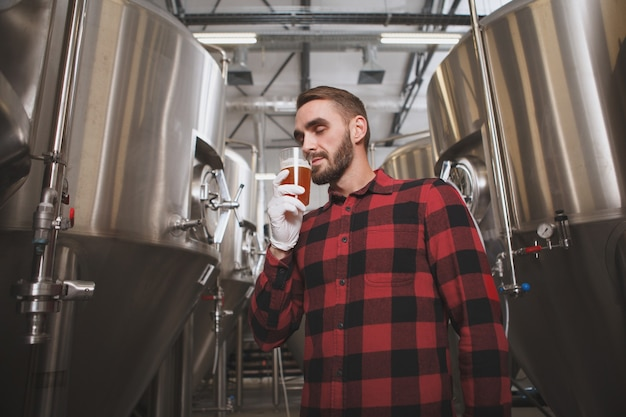 Lage hoek die van een knappe brouwer is ontsproten die heerlijk bier ruikt