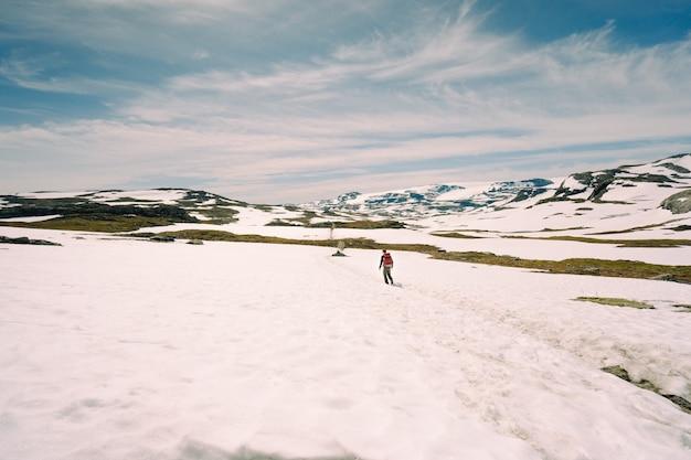 Lage hoek die van een man is ontsproten die op besneeuwde heuvels loopt