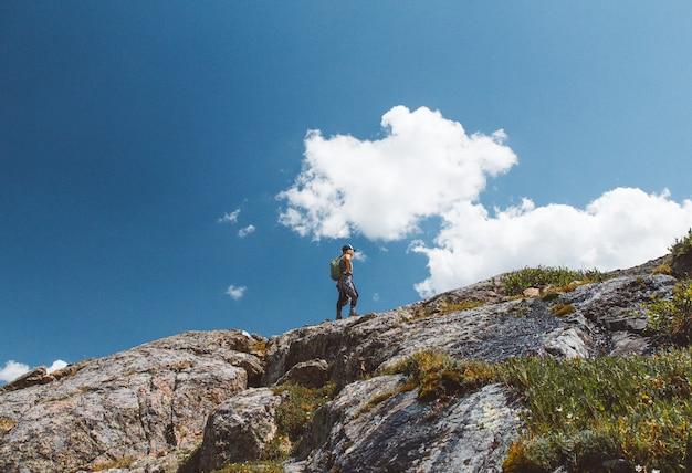 Lage hoek die van een mannetje met een rugzak is ontsproten die zich op de rand van de berg onder bewolkte hemel bevindt