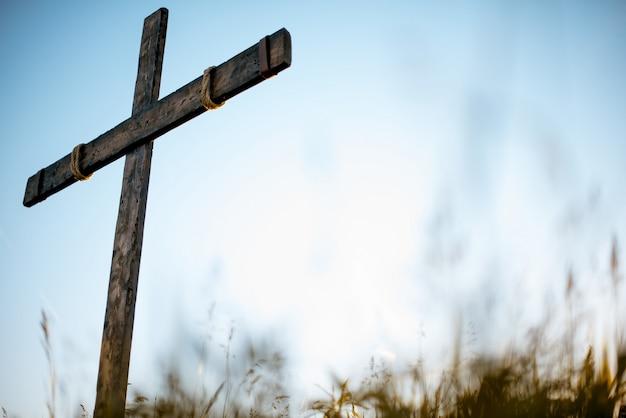 Lage hoek die van een met de hand gemaakt houten kruis in een grasrijk gebied met een blauw is ontsproten