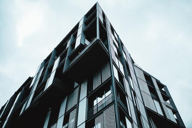 Lage hoek die van een modern gebouw met glasramen is ontsproten
