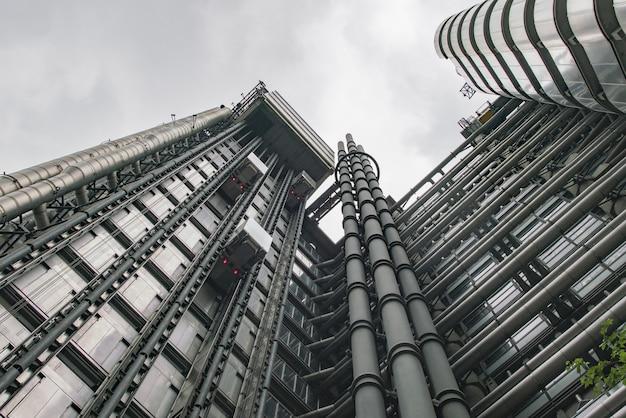 Lage hoek die van een modern grijs gebouw met glasvensters onder de duidelijke hemel is ontsproten