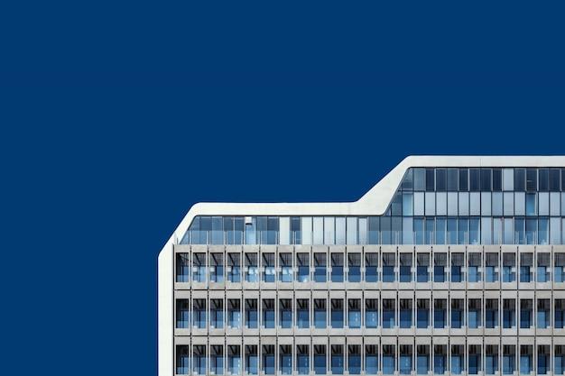 Lage hoek die van een mooi glasgebouw onder de blauwe hemel is ontsproten