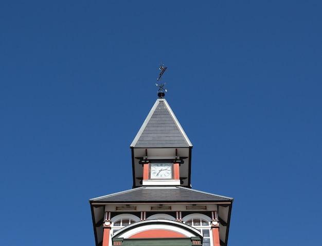 Lage hoek die van een mooie toren op blauwe hemel is ontsproten