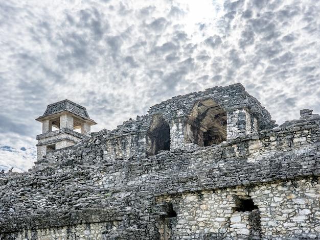 Lage hoek die van een oud gebouw onder een bewolkte hemel overdag is ontsproten