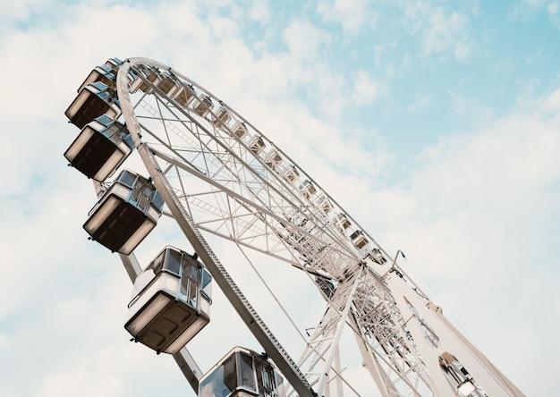 Lage hoek die van een reuzenrad met bewolkte blauwe hemel is ontsproten