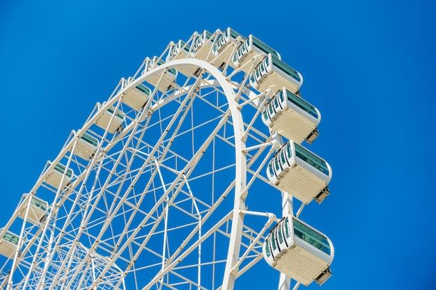 Lage hoek die van een reuzenrad onder een duidelijke blauwe hemel is ontsproten