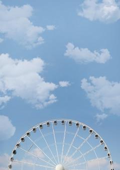 Lage hoek die van een reuzenrad op bewolkte hemel is ontsproten