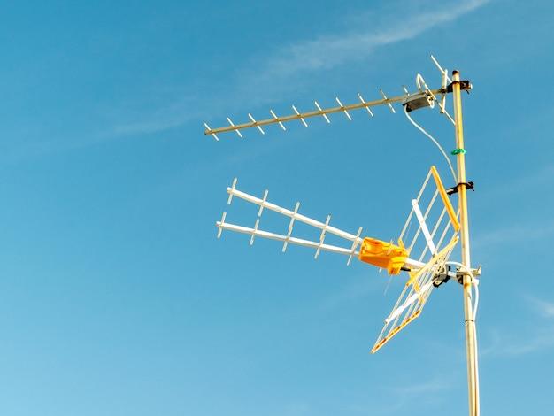 Lage hoek die van een televisieantenne is ontsproten die op een zonnige dag met een duidelijke hemel wordt vastgelegd
