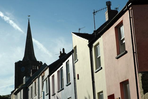 Lage hoek die van een toren dichtbij roze en blauwe geassorteerde gebouwen is ontsproten