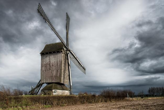 Lage hoek die van een windmolen in een grasrijk gebied onder de adembenemende onweerswolken is ontsproten