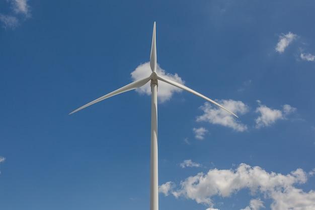 Lage hoek die van een windmolen onder het zonlicht en een blauwe hemel overdag is ontsproten - milieuconcept