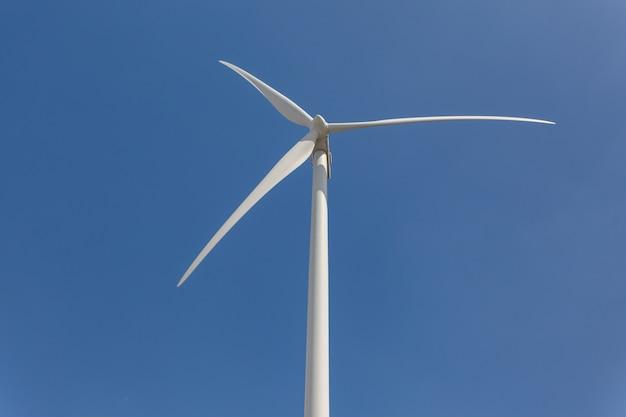 Lage hoek die van een windmolen onder het zonlicht en een blauwe hemel overdag is ontsproten