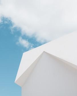 Lage hoek die van een wit gebouw onder een wolk en een blauwe hemel is ontsproten