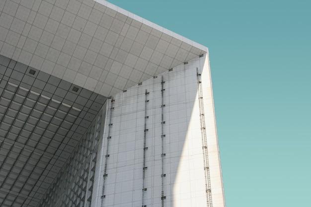 Lage hoek die van een wit modern gebouw onder de blauwe hemel is ontsproten