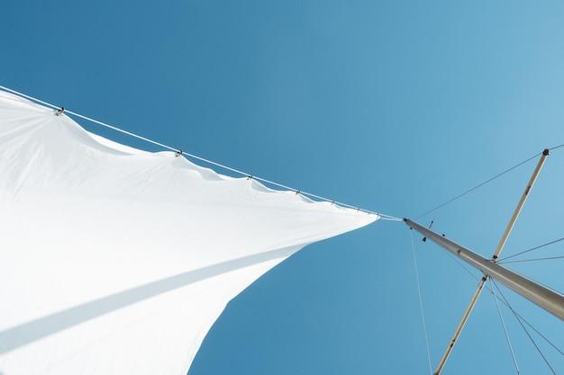 Lage hoek die van een wit zeil op bootmast is ontsproten onder duidelijke hemel overdag