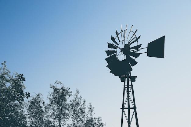 Lage hoek die van het silhouet van een windmolen over de bomen is ontsproten