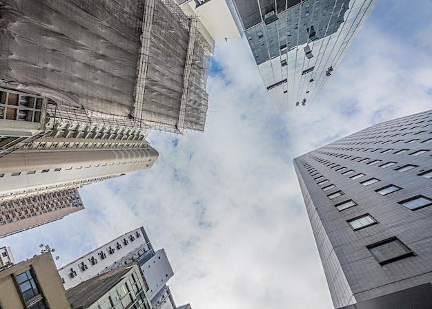 Lage hoek die van hoge woongebouwen onder de bewolkte hemel is ontsproten