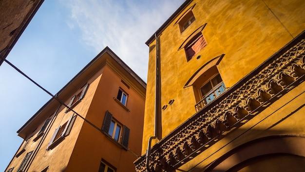 Lage hoek die van oranje gebouwen met vensters in italië is ontsproten