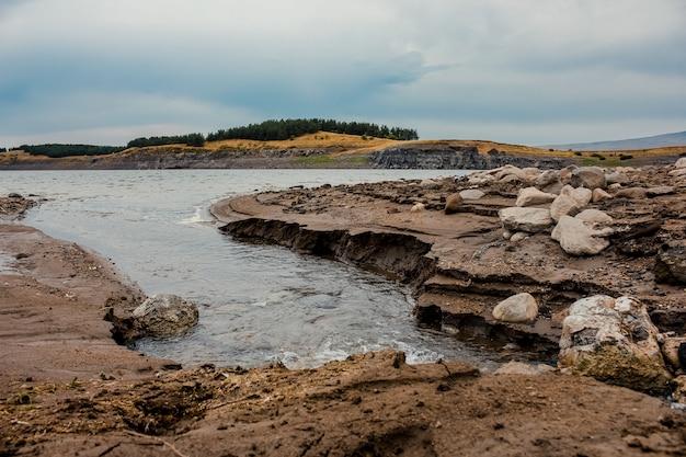 Lage hoek die van rotsachtige oever van het meer met donkere wolken in het voorjaar is ontsproten