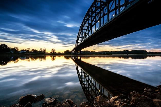 Lage hoek die van sydney harbour bridge in australië tijdens zonsondergang is ontsproten