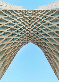 Lage hoek die van the arc van azadi-toren in teheran met blauwe hemel is ontsproten
