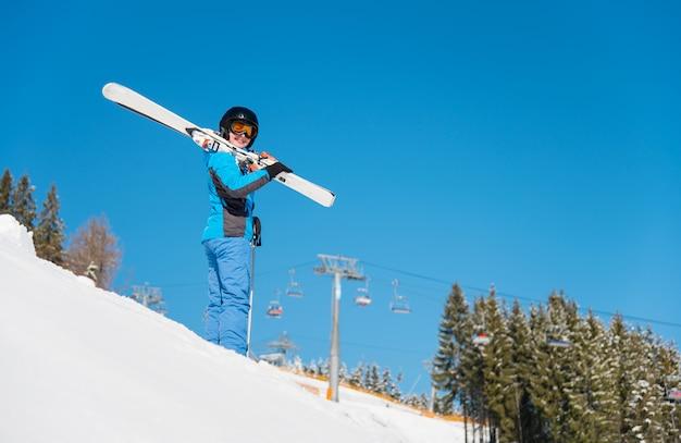 Lage hoek die van vrouwelijke skiër op de heuvel in sneeuwbergen is ontsproten die haar skis op de schouder houdt. blauwe hemel, winter bos en skigebied
