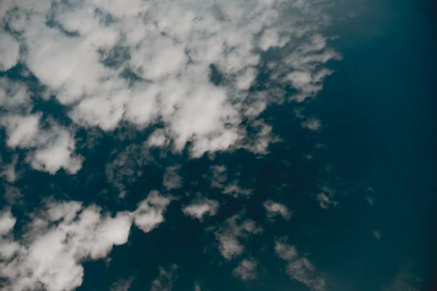Lage hoek die van wolken in een donkerblauwe hemel is ontsproten