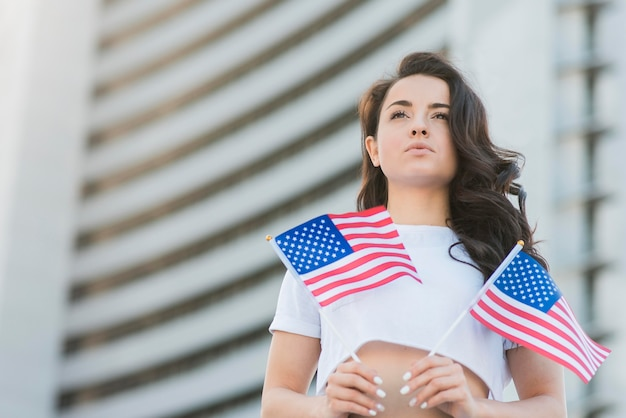 Lage hoek donkerbruine vrouw die twee vlaggen van de vs houdt