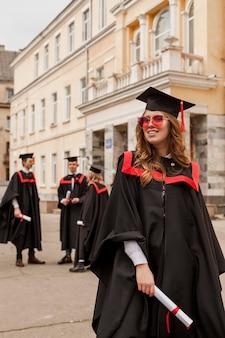Lage hoek gelukkig meisje afgestudeerd