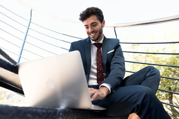 Lage hoek gelukkige advocaat met zijn laptop