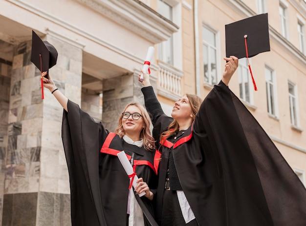 Lage hoek gelukkige meisjes met diploma