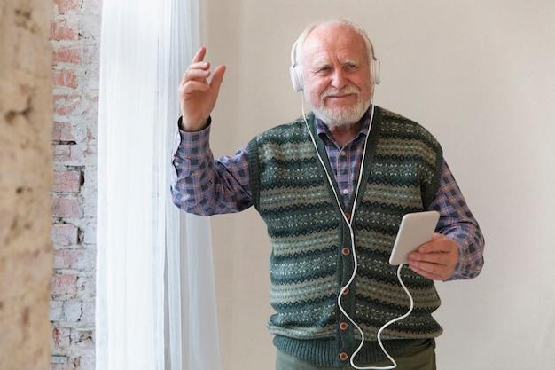 Lage hoek gelukkige oudste die de muziek leeft