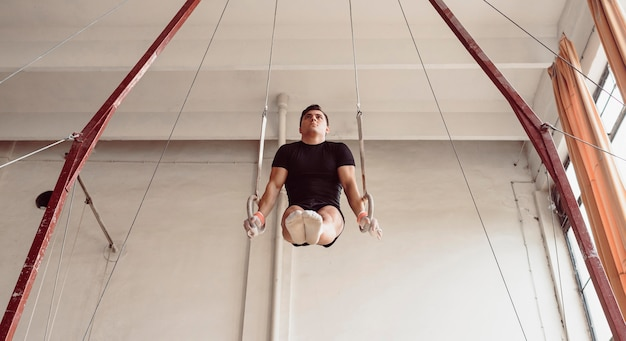 Lage hoek jonge man training op gymnastiek ringen