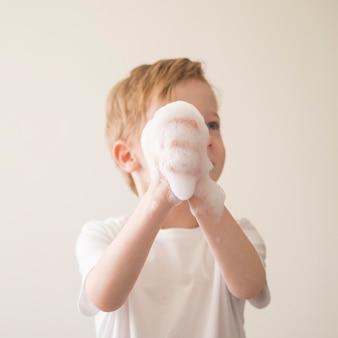 Lage hoek jongen met schuim op handen