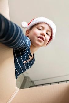 Lage hoek kleine jongen op zoek in een geschenkdoos