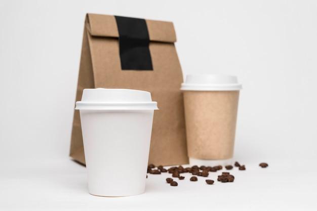 Lage hoek koffiekopjes en papieren zak