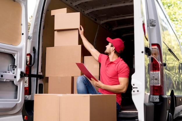 Lage hoek levering man met pakketlijst