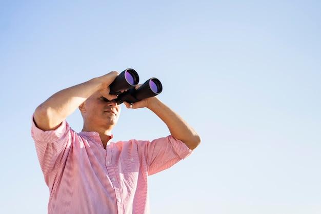 Lage hoek man kijken via verrekijker