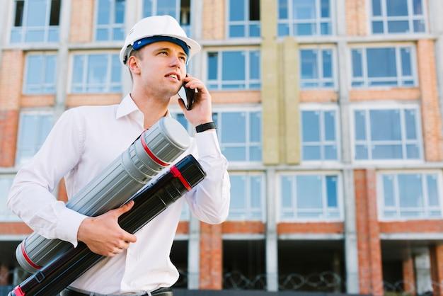 Lage hoek man met helm praten aan de telefoon
