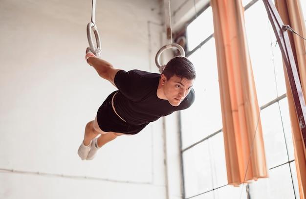 Lage hoek man training op gymnastiek ringen