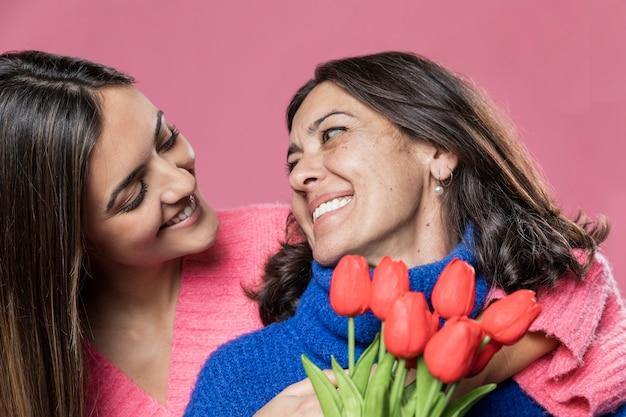Lage hoek meisje verrassende moeder met bloemen