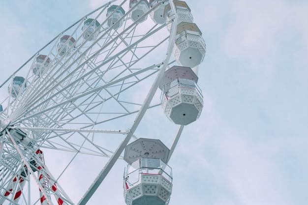 Lage hoek mening van de reuzenrad carrousel overdag onder een blauwe hemel