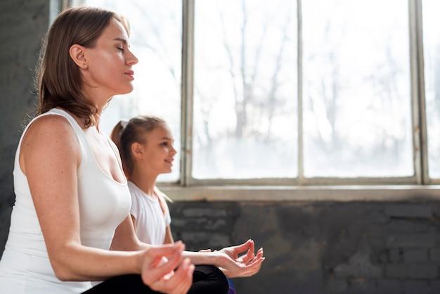 Lage hoek moeder en dochter mediteren