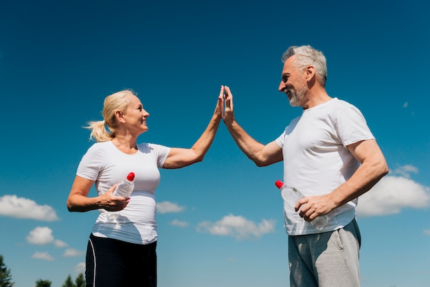 Lage hoek oude mensen high fiving