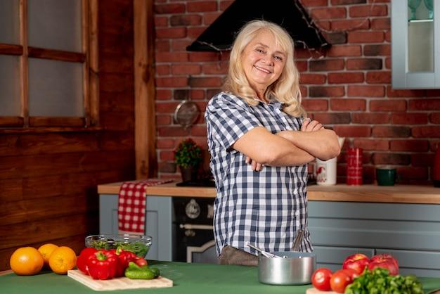 Lage hoek oudere vrouw in keuken het koken