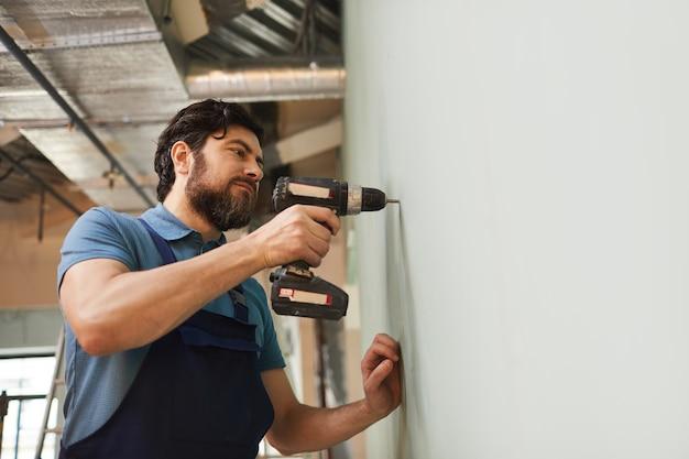 Lage hoek portret van bebaarde bouwvakker boormuur tijdens het renoveren van huis alleen, kopie ruimte