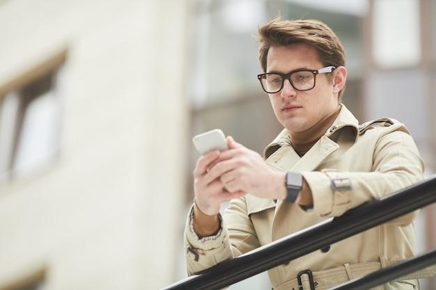 Lage hoek portret van moderne jonge zakenman trenchcoat dragen en smartphone houden terwijl leunend op reling buitenshuis in stedelijke stad omgeving, kopie ruimte