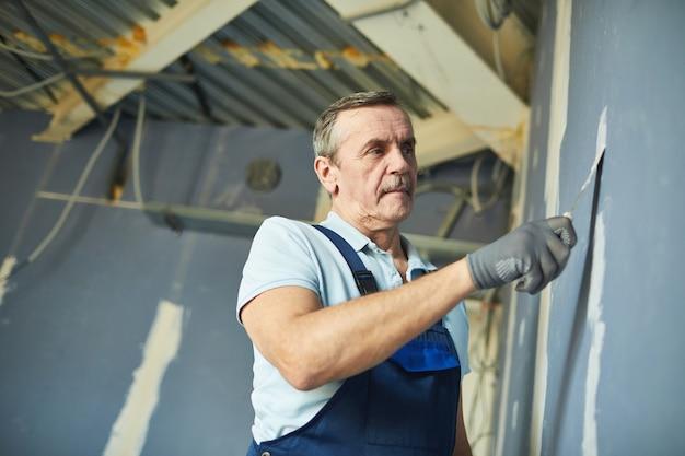 Lage hoek portret van senior man aan het werk op droge muur tijdens het renoveren van huis, kopieer ruimte