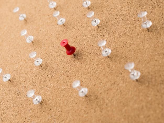 Lage hoek rode pin omgeven door witte pinnen op een houten bord